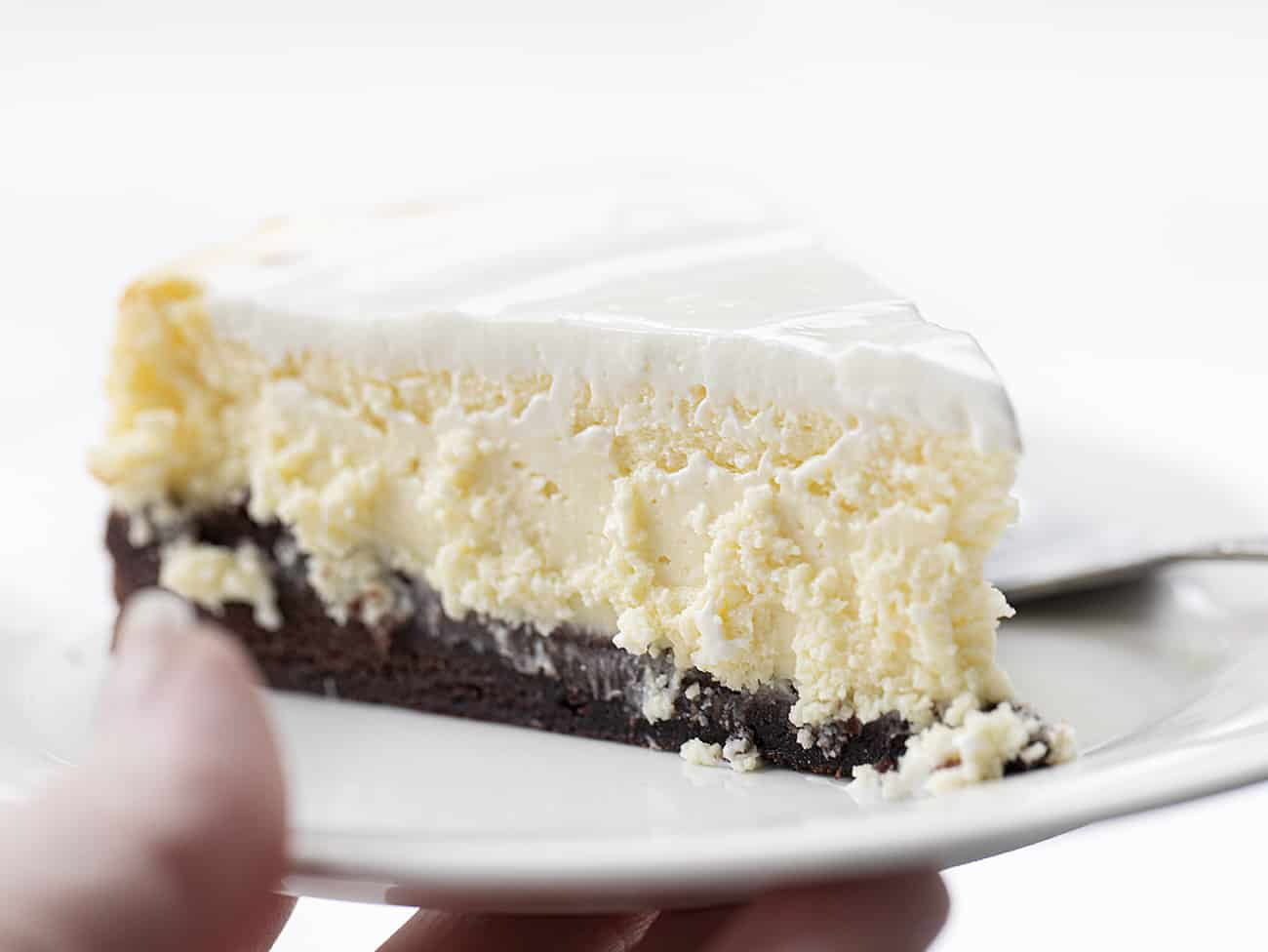 Hand Holding White Plate with Brownie Bottom Cheesecake Recipe with Sour Cream Frosting Topping and Fork Resting Next to It