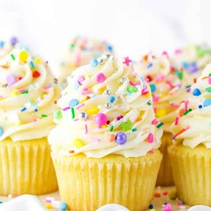 Pinterest image for vanilla cupcakes showing a close up of cupcakes and a stack of cupcakes on a white stand