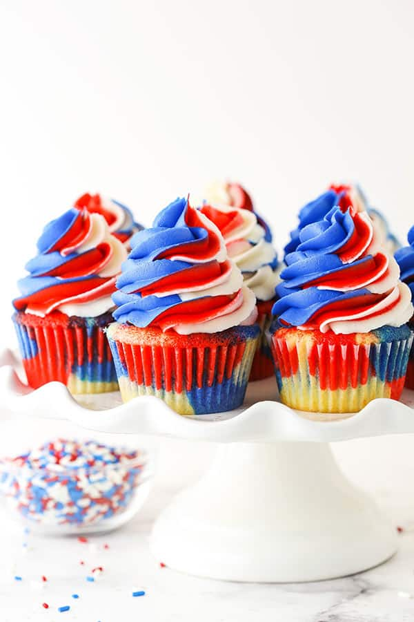 pinterest image for red, white and blue cupcakes - cupcakes on a white cake stand and one with a bite out