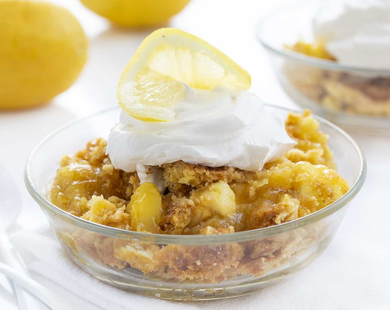 One Bowl of Lemon Cream Cheese Dump Cake with Whipped Cream and a Lemon Slice on Top